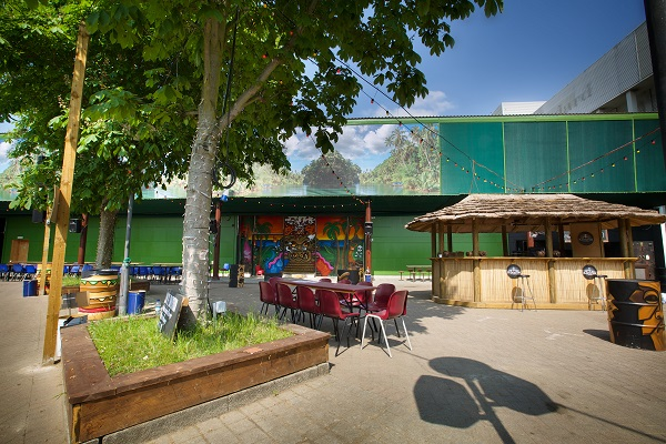 Hawker House Summer Party SE1. Outside space with grass verge and warehouse containers around outside space.