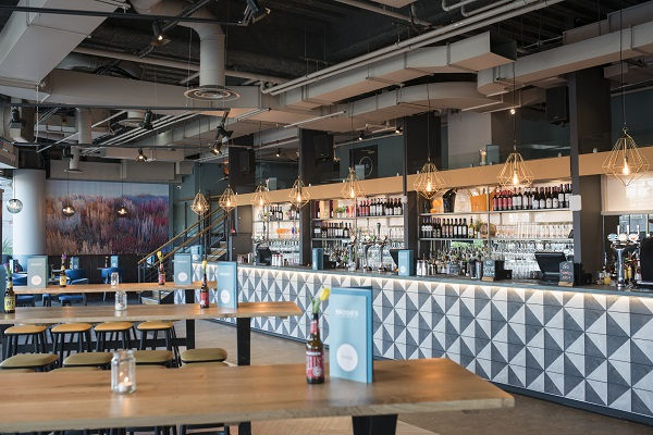 Brodies Bar and Kitchen Venue Hire E14. Image of the bar with high tables and chairs for guests to sit and enjoy their event.