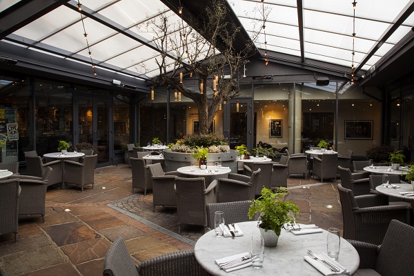 Hoxton Grill Christmas party EC2A. conservatory of venue with fireplace and tables and lounge chairs