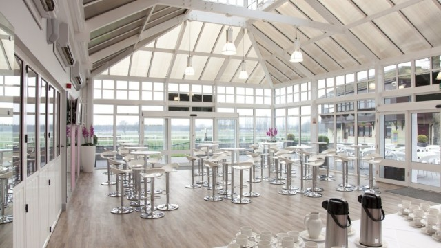 Haydock Racecourse Shared Christmas Party WA12 inside venue with tables and chairs and large windows.