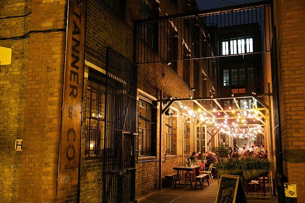 Tanner & Co Summer Party SE1- Outside courtyard with summer party guests in the evening