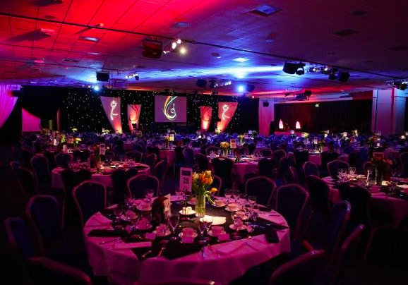 A purple and red ulighted function room in the venue complete with round tables, Christmas novelties and a screen situated at the front of the event space.